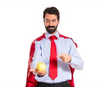 Homme d'affaires habillé comme un super-héros tenant une pomme