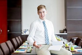 Homme d'affaires souriant assis sur une table de conférence