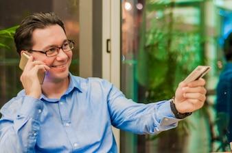 Homme d'affaires souriant parlant avec un téléphone intelligent et Giving Card to Waiter in Cafe