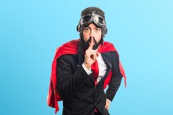 Homme d'affaires super héroïne faisant silence geste sur fond coloré