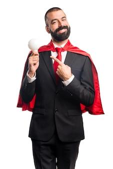 Homme d'affaires super héroïne tenant une ampoule