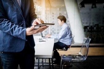Homme d'affaires travaillant avec tablette dans le bureau, closeup
