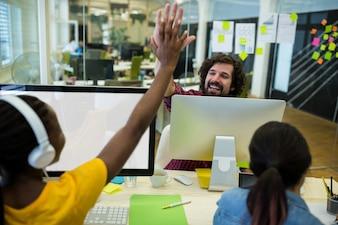 Homme designer graphique donnant cinq de haut à son collègue