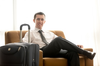 Homme élégant assis dans un fauteuil