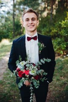 Homme en smoking avec bouquet souriant