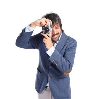Homme photographiant sur fond blanc