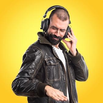 Homme portant une veste en cuir, écoutant de la musique sur un fond coloré