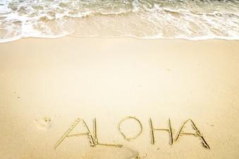 Inscription Aloha écrit sur la plage de sable avec de l'océan - espace libre. effet de couleur de couleur vintage