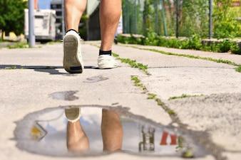 Jambes en marchant. Réflexions dans l'eau sur le trottoir.