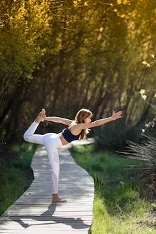 Jeune belle femme faisant du yoga dans la nature