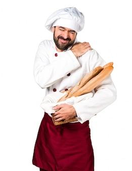 Jeune boulanger tenant du pain avec une douleur à l'épaule