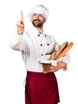 Jeune boulanger tenant un pain touchant sur un écran transparent