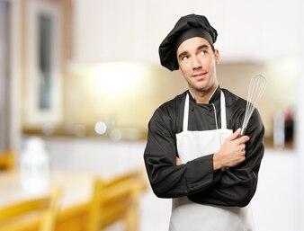 Jeune chef utilisant un ustensile de cuisine avec un geste de doute