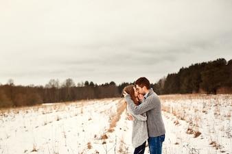 Jeune couple étreintes et baisers dans une prairie solitaire