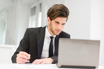 Jeune employé travaillant sur son rapport