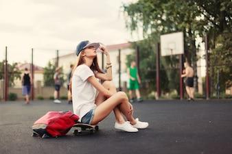 Jeune femme avec chapeau et planche à roulettes