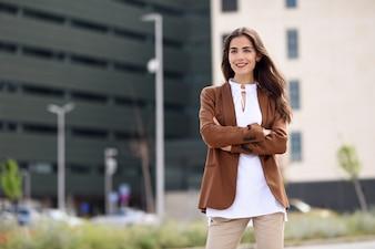 Jeune femme avec de beaux cheveux debout à l'extérieur du bâtiment de bureaux.