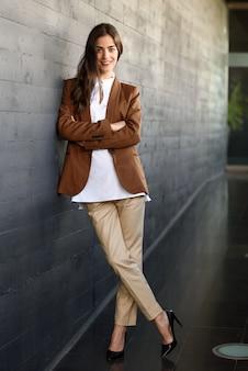 Jeune femme d'affaires debout à l'extérieur du bâtiment de bureaux.