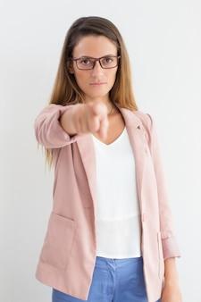 Jeune femme d'affaires sérieuse pointant vers la caméra