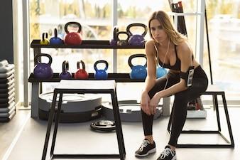 Jeune femme écoutant de la musique avec un smartphone assis à la gym
