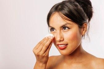 Jeune femme enlevant son maquillage avec un coton
