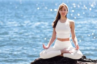 Jeune femme faisant du yoga dans la plage vêtu de vêtements blancs