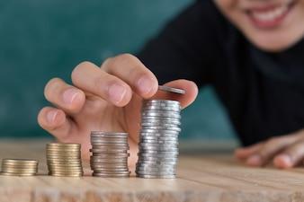 Jeune femme heureuse insérer la pièce sur l'empilé de pièces de monnaie sur le bureau