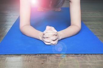 Jeune femme planche sur le tapis de yoga bleu à la maison, Travailler et concept de mode de vie