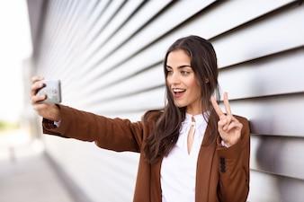 Jeune femme prenant une photographie selfie avec un téléphone intelligent faisant V sig