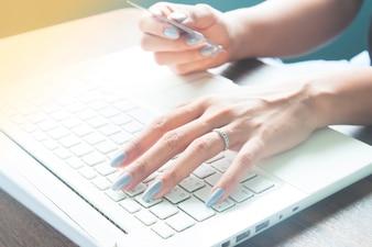 Jeune femme utilisant un ordinateur portable et une carte de crédit pour les achats en ligne