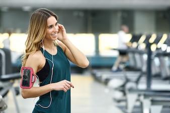 Jeune femme utilisant un smartphone debout dans la salle de gym