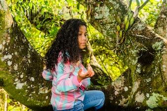 Jeune fille assise sur un arbre