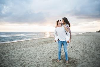 Jeune fille avec une couverture sur le dos de son petit ami sur la plage