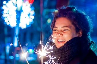 Jeune fille souriante tenant un sparkler dans sa main. Adolescent souriant dans la rue la nuit avec des étincelles