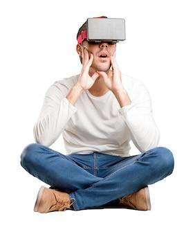 Jeune homme assis en utilisant des lunettes de réalité virtuelle