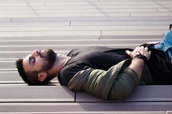 Jeune homme beau couché sur les escaliers, relaxant