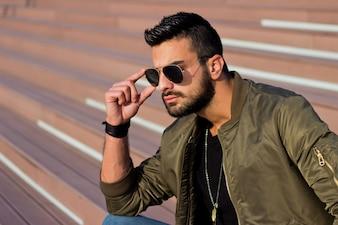 Jeune homme beau regardant la vue de la ville, lunettes de soleil