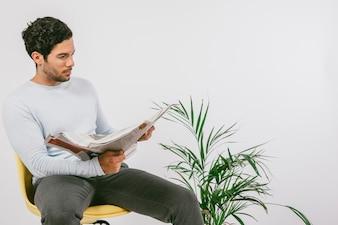 Jeune homme lisant le journal