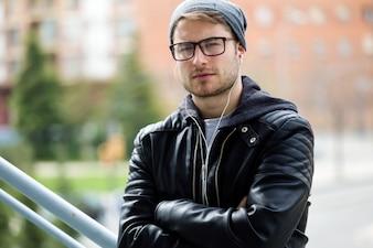 Jeune homme moderne regardant la caméra dans la rue.