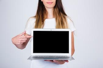 Jeune modèle tenant et pointant portable