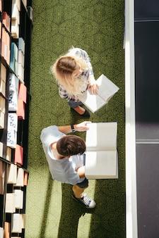 Jeunes gens lisant dans la bibliothèque