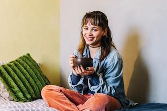 Jolie femme mangeant au lit
