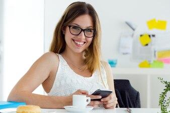 Jolie jeune femme qui utilise son téléphone mobile à la maison.