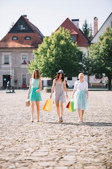 Jolies femmes marchant avec des sacs en papier