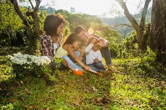 Joyeuse famille assise dans l'herbe