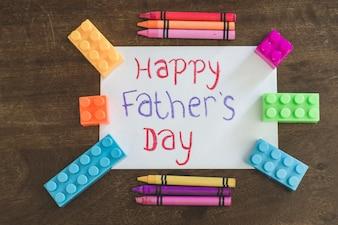 L'écriture du jour du père avec des crayons et des briques de jouets