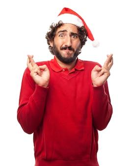 L'homme avec un chapeau de Père Noël et croisant les doigts