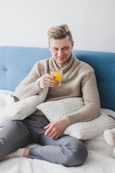 L'homme boit un jus assis sur le lit