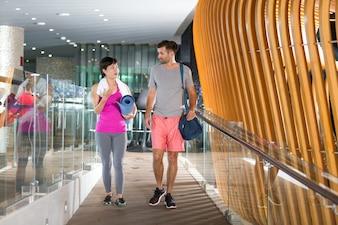 L'homme et la femme de quitter la salle de gym