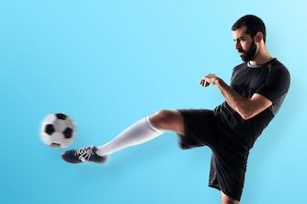 L'homme joue au football sur un fond coloré